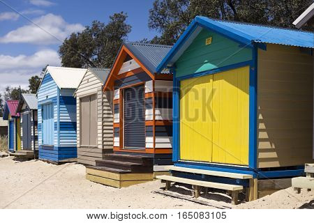 MELBOURNE, AUSTRALIA - January 11, 2017: The rainbow coloured bathing boxes are a symbol of summer and a tourist attraction of the Mornington Peninsula south of Melbourne Australia