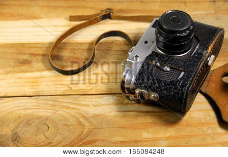 Old retro camera in leather case on the wooden background