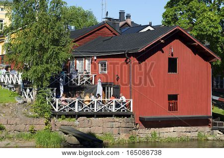 PORVOO, FINLAND - JUNE 13, 2015: A view of summer cafe on the river bank of Porvoyoki in the old city Porvoo. Historical landmark