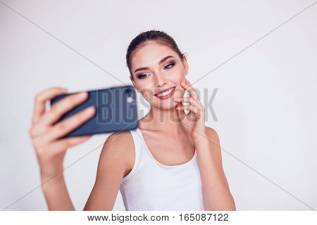 Beautiful brunette girl with makeup make selfie on white background, isolated.