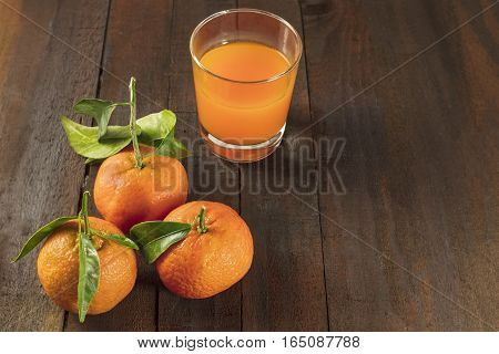 A photo of vibrant orange tangerines with green leaves and a glass of fresh pressed juice on a dark wooden boards texture with copyspace