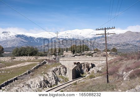 Rail road. At the background, snow capped peaks of the Guadarrama Mountains. Photo taken in Colmenar Viejo Madrid Province