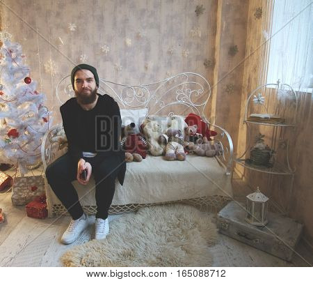 Funny man with a beard. Handsome guy in a New Year's interior. Christmas card with a guy. Space for text