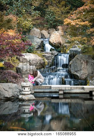 London, UK - November 3 2016: Woman and child at scenic Japanese style gardens with a waterfall in Holland park London