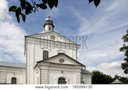 Christian orthodox white church with silver domes and gold crosses
