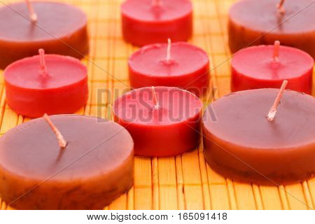 Many candles on bamboo mat background, close up picture.