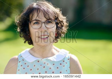 portrait of a middle-aged woman with glasses in the garden