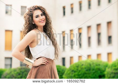 Beautiful woman with curly hair. Urban look. A beautiful and happy young woman. White shirt sleeveless and brown skirt. Gold bracelet.