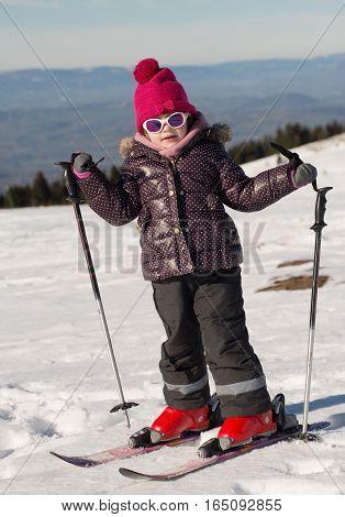 a happy little pretty girl skiing downhill
