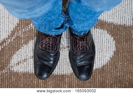 Close up men wear blue jean and brown leather shoes on floor.