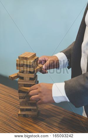Businessman Gambling Placing Wooden Block On A Tower - Planning, Risk And Strategy In Business