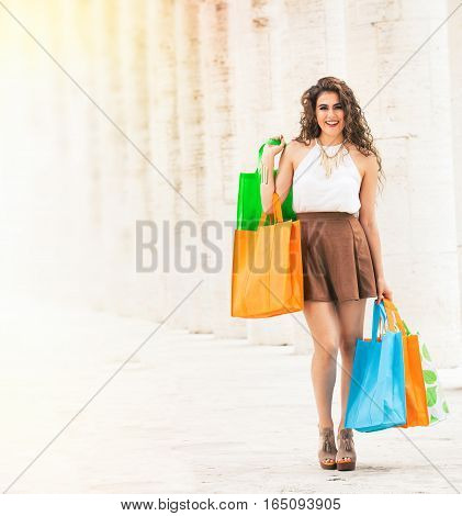 Shopaholic. Shopping love. Beautiful happy woman with bags. A happy and smiling woman just went shopping. Beautiful smile. Colored bags in hand. Long curly hair and stylish clothes. Outdoors on the white marble columns background.