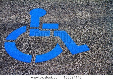 Handicap Parking Emblem painted in Blue paint in a parking lot.