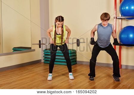 Coach man explains the exercises with barbell for a girl. Personal coach. Healthy lifestyle concept. Fitness.