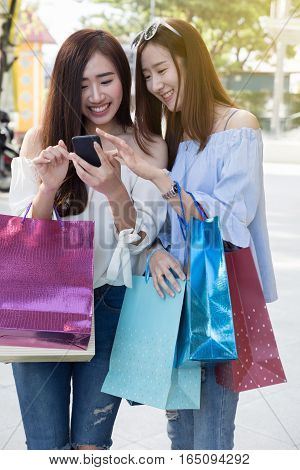 Happy Asian Woman With Smartphone And Colorful Shopping Bags At Department Store Shopping Mall