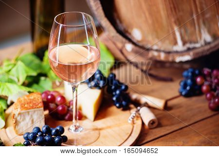 Wine glass, cheese, grapes and wooden barrel
