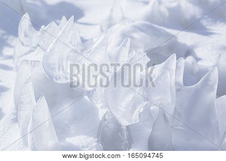 Whimsical surface ice with snow closeup on blue sky background. Copy space. Texture.