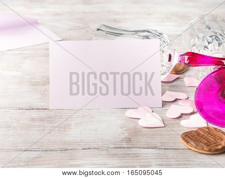 Empty pink paper note with two stemmed champagne glasses pink hearts and chocolate cookies on wooden textured background. Valentine's day wedding romantic date invitation