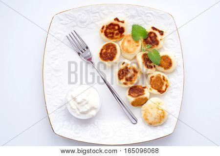 cheesecakes with sour cream on a white plate
