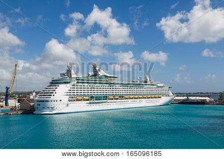 A white luxury cruise ship docked at the freight yard in Bridgetown Barbados