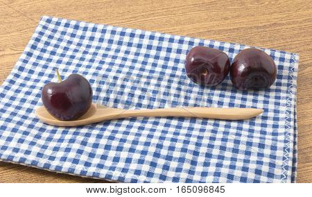 Fresh Fruits Pile of Ripe and Sweet Red Plums A Very Good Source of Vitamin C on Blue and White Checked Towel.