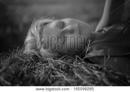 Sexy woman on hay stack on sunset. Beauty romantic girl outdoors against hay stack. Photo of sexy blond in a field with haystacks. Toning photo