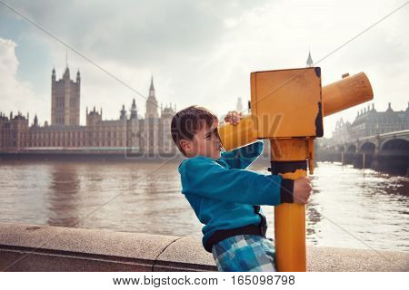 Child looking through coin operated high powered binoculars. View of the Palace of Westminster from the Thames