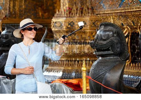 Young woman with hat and sunglasses making a self portrait with action camera, in Grand Palace, Bangkok