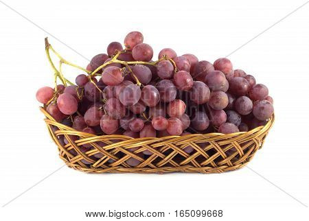 Red wine grape berries on branch in long brown wicker basket front view isolated on white close up