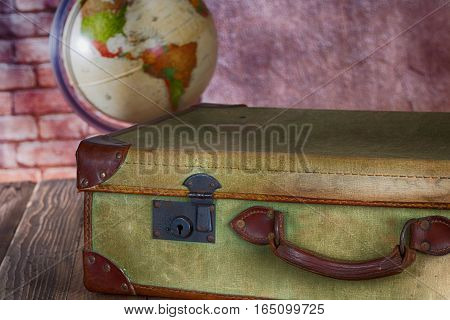 Antique suitcase with ball of the world to choose travel destination