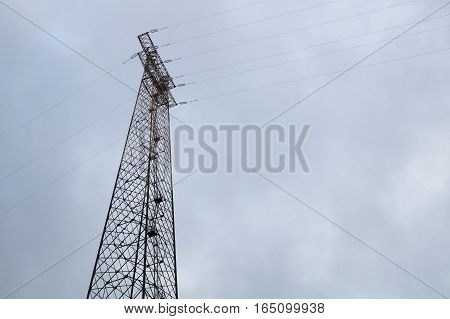 Silhouette of electricity post on blue sky background, low angle shot, high voltage electric pole, high voltage power supply on cloudy day.