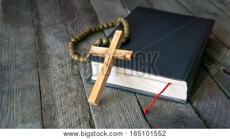 Wooden cross, Holy Bible and vintage rosary beads.