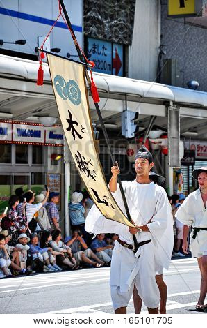 Kyoto Japan - July 17 2011: Japanese Young Man Holing Flag Leading the Parade in Gion Festival Kyoto Japan