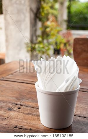 Napkin or tissue paper in a cup on a wooden table