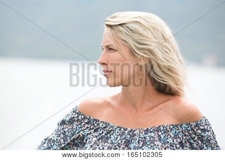 Portrait of beautiful long haired blonde woman outdoor, sexy shoulders.