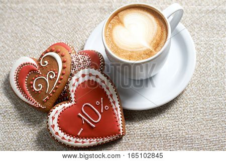 Love potion. High angle shot of a cup of frothed coffee and Valentine s day heart shaped cookies on the cafe table