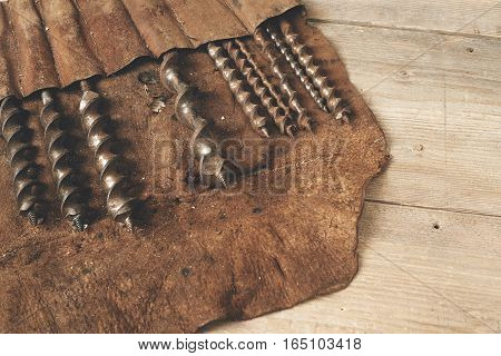 Drill bits in leather tool roll on wooden workbench