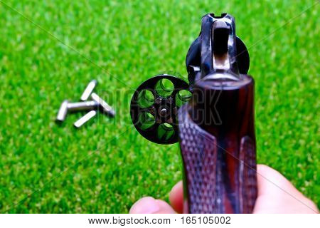 Revolver gun in hand on grass background