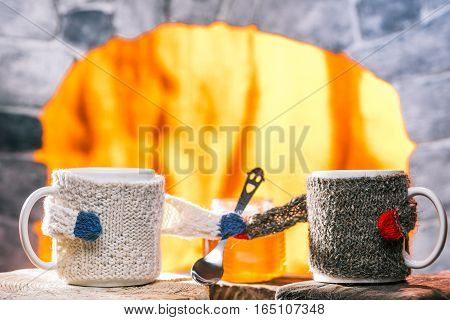 Tea mugs in sweater cozies holding teaspoon in their hands. Fire in oven on the background