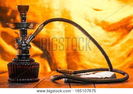 Hookah on the table. Little wood tray for drink or asseccories. Fire background