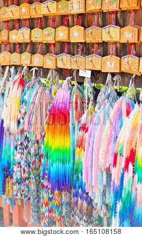 Ema prayer tablets and strings of paper origami cranes. Wishes written in Japanese on the plaques. Fushimi Inari Kyoto.