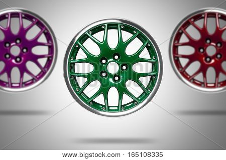 Colorful alloy rims floating in the air at grey background