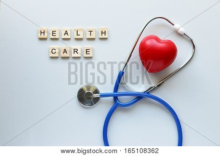 Healthcare text word made with wood blocks and Red Heart,stethoscope on table.Concept healthcare