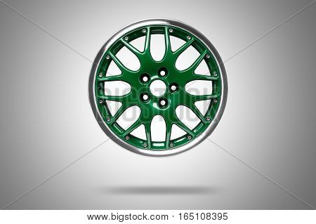 Green alloy rim floating in the air at grey background