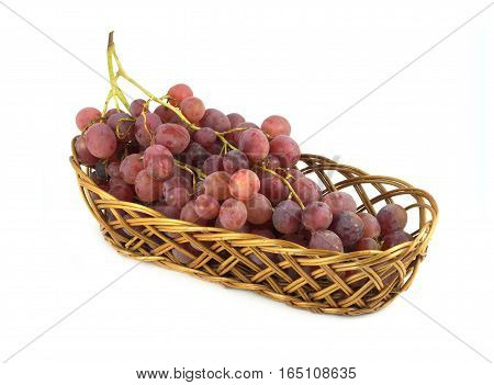 Red grape on branch in brown wicker basket isolated on white side view