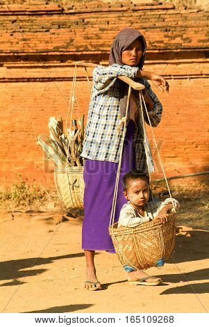 Bagan Myanmar - 24 January 2010: Woman with her son on a basket at the archaeological site of Bagan on Myanmar