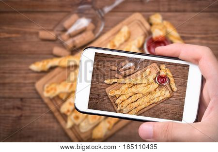 Hands taking photo puff pastry cheese twists with smartphone.
