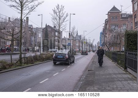 Amsterdam Nederland- December 302016: In the streets of the ancient city tourists move and transport.In the foreground is an old man