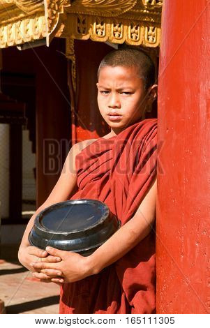 Bagan Myanmar - 8 February 2010: Young monk with a rice container at Shwezigon pagoda at the archaeological site of Bagan on Myanmar