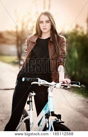 outdoor portrait of pretty young woman with bicycle in a park